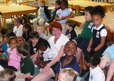 Bonnie Simpson, Orchid Rotary Club, sits with children during the Josh the Otter reading.